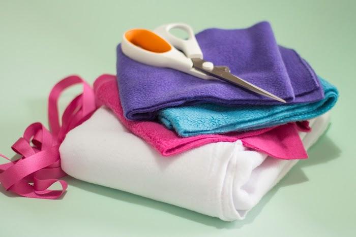 materiallien für ein selbstgebasteltes weißes einhorn, eine weiße schere und eine pinke schleife, ein steckenpferd einhorn selber basteln