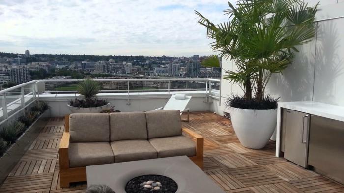 ausgefallener Tisch mit Flusssteine in der Mitte, großer Zierbaum, Terrasse dekorieren