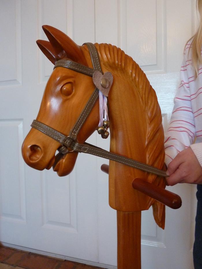 ein großes steckenpferd mit einem kleinen braunen herzen, ein jungesmädchen und ihr selbstgebastelten pferd aus holz, holz zum basteln