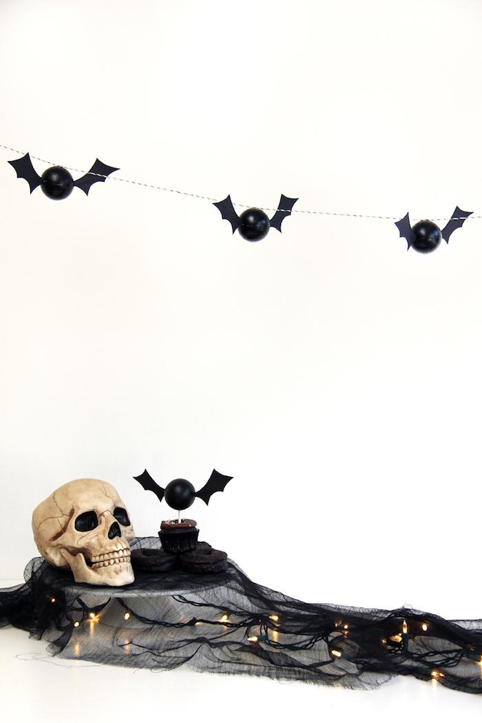 basteln mit papier, eine dekoration mit kleinen schwarzen fliegenden selbstgebastelten fledermäusen aus schwarzen kleinen bällen und mit schwarzen flügeln und einem weißen totenkopf mit schwarzen augen