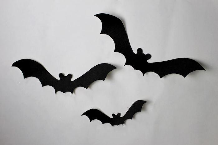 drei kleine schwarze fliegende fledermäuse aus papier, eine weiße wand mit einer halloween dekoration mit selbstgebastelten schwarzen fledermäusen mit schwarzen flügeln und ohren, eine fledermaus malen