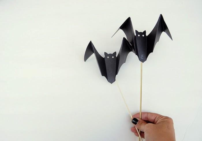 eine hand mit einem schwarzen nagellack und mit zwei kleinen schwarzen fledermäusen aus papier, kleine origami fledermäuse mit schwarzen flügeln und kleinen weißen augen und schwarzen ohren