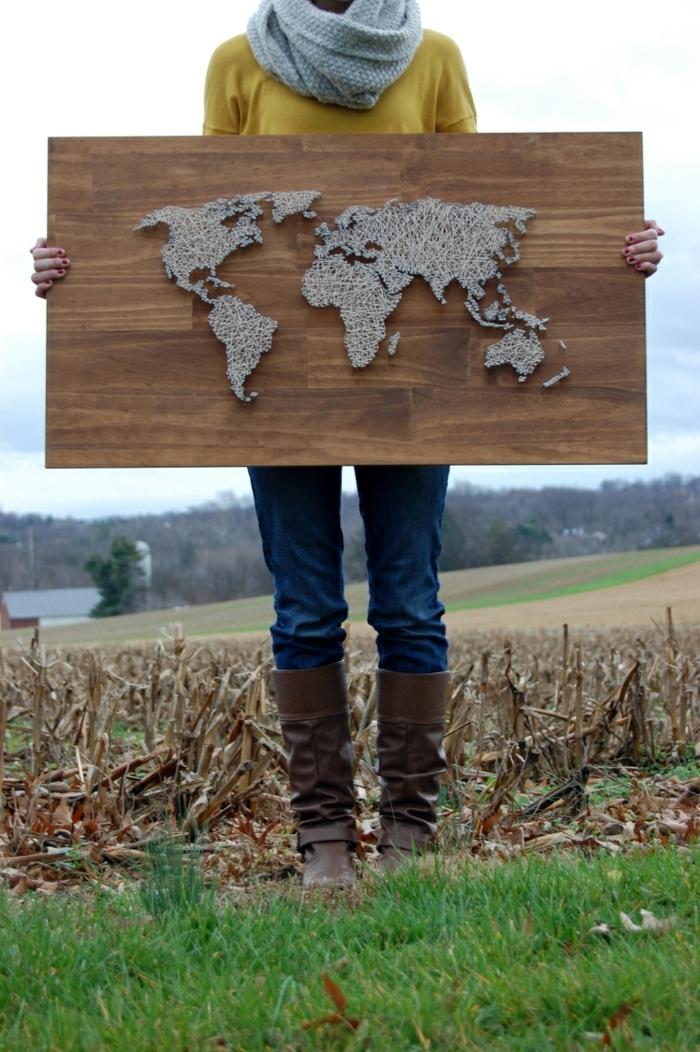 das Mädchen ist stolz auf Ihre Fadenkunst, eine große Weltkarte auf hölzerne Tafel