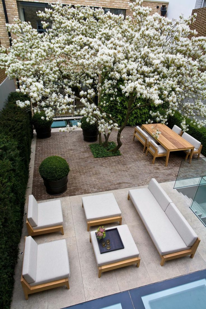 ein weiß blühender Baum, weiße Loungmöbel, prächtige Terrassenbepflanzung