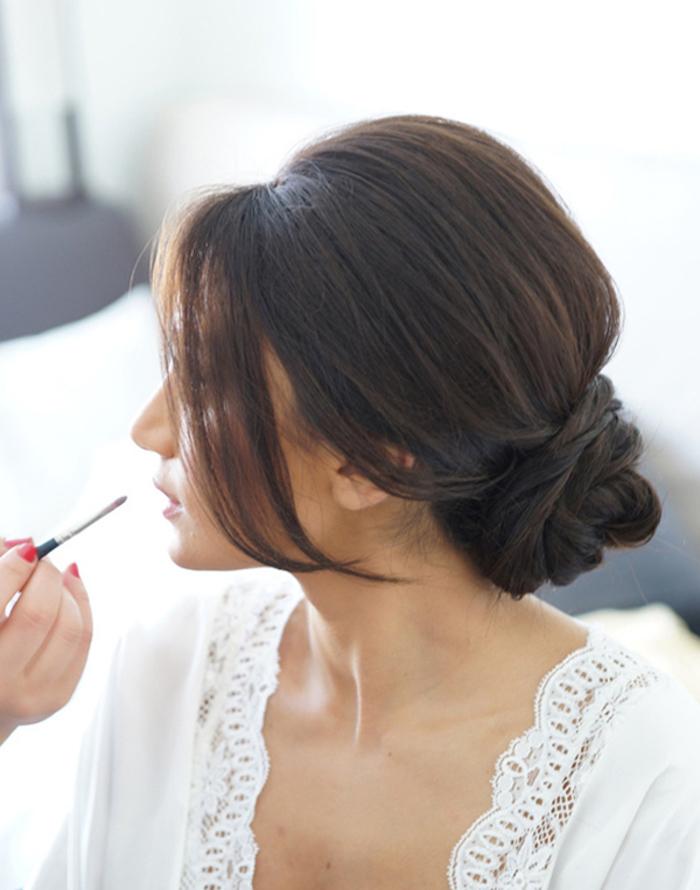 Einfache und elegante Dutt Frisur mit locker fallenden Strähnen, olivfarbener Teint