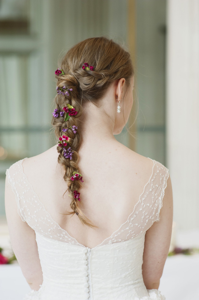 Zopf verziert mit echten Blumen, Brautkleid mit Spitzenelementen, kastanienbraune lange Haare