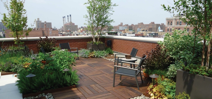 drei grüne Bäume, einige schwarze Stühle, grüne Terrassenpflanzen, braune Diele