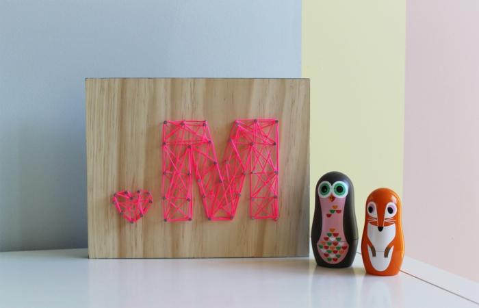 ein M Buchstabe und ein kleines Herz von rosa Faden, ein perfektes Mutterstaggeschenk