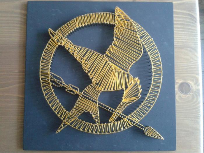 eine Abbildung vom Logo des Films Tribute von Panem, gelbes String Art Bild