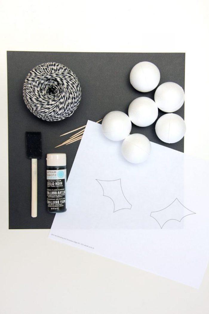 kleine weiße bälle und ein blatt papier mit kleinen weißen fledermaus flügeln, kleber und viele kleine zahnstocher und faden
