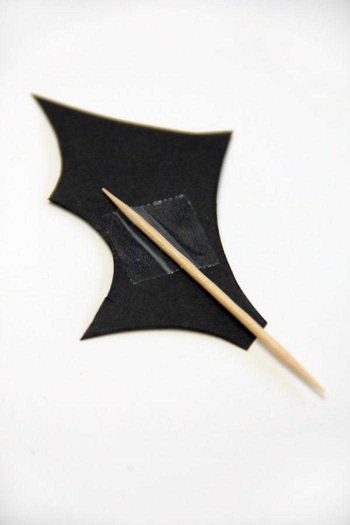 ein kleiner gelber zahnstocher mit einem schwarzen fledermaus flügel aus papier, eine fledermaus selber machen