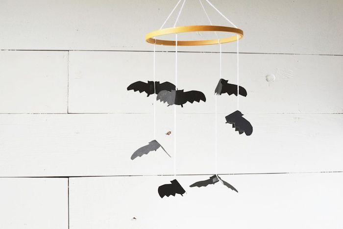 ein baby-mobile mit vielen kleinen schwarzen fledermäusen mit schwarzen ohren und flügeln, selbstgebastelte fledermaus aus papier und eine weiße wand, basteln mit papier