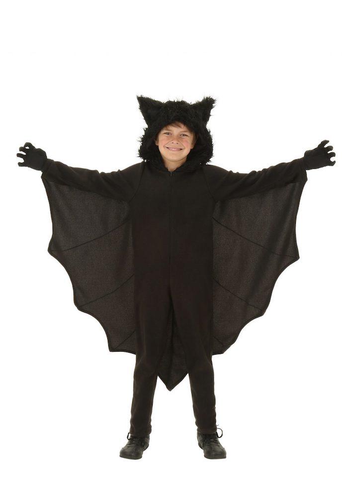 ein kind mit einem großen schwarzen fledermaus kostüm mit schwarzen flügeln und schwarzen ohren, ein fledermaus kostäm kinder. fledermaus häkeln