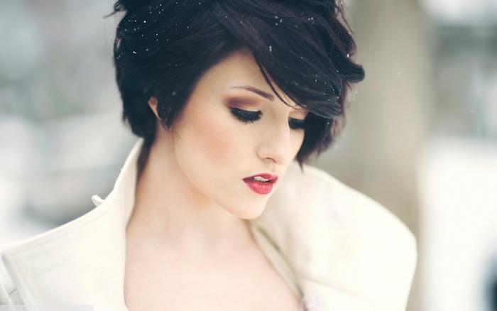 Smokey Eyes und Porzellanteint, knallroter Lippenstift, schwarze kurze Haare, weißer Mantel
