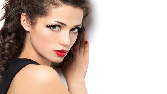 Lange künstliche Wimpern, roter Lippenstift und Porzellanteint, schwarze Haare mit Locken, roter Nagellack