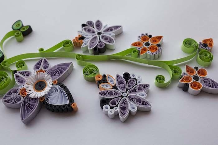 kleine und große violette und grüne quilling blumen mit grünen, violetten, weißen und orangen quilling papierstreifen