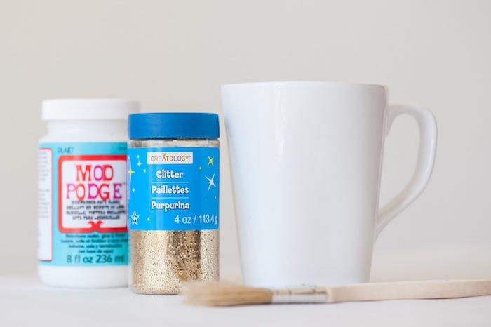 Funkelnde Tassen selber machen, dazu brauchen Sie weiße Porzellantassen, Kleber und goldenen Glitzer