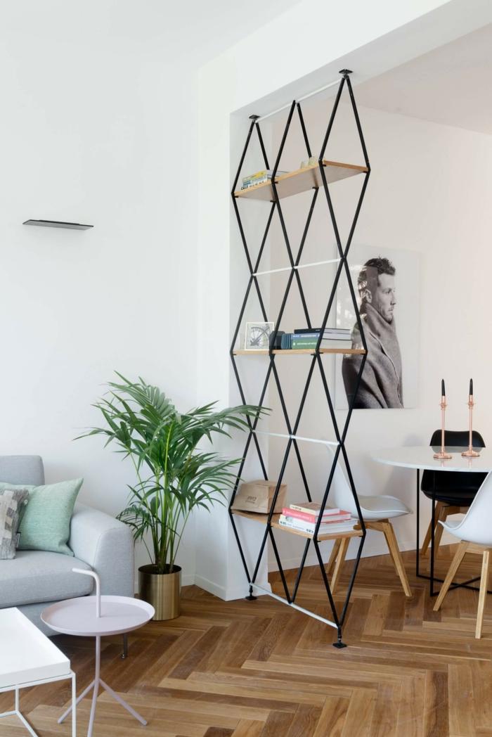 Trennwand Wohnzimmer aus Stahl, ein Gitter trägt Bretten als Regalen