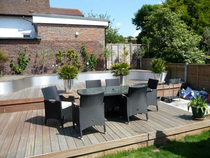 ein schwarzer Tisch mit schwarze Rattan Stühle, Terrassendiele und Blumenkübel bepflanzen
