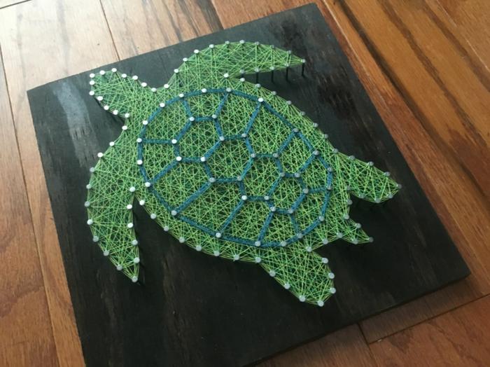 eine grüne Schildkröte, ein schwarzes Brettchen, String Art Bild zum Bewundern