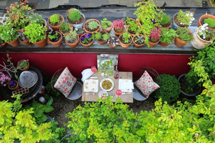 eine bunte Terrasse, zwei Stühle mit bunten Kissen dekoriert, Terrasse bepflanzen
