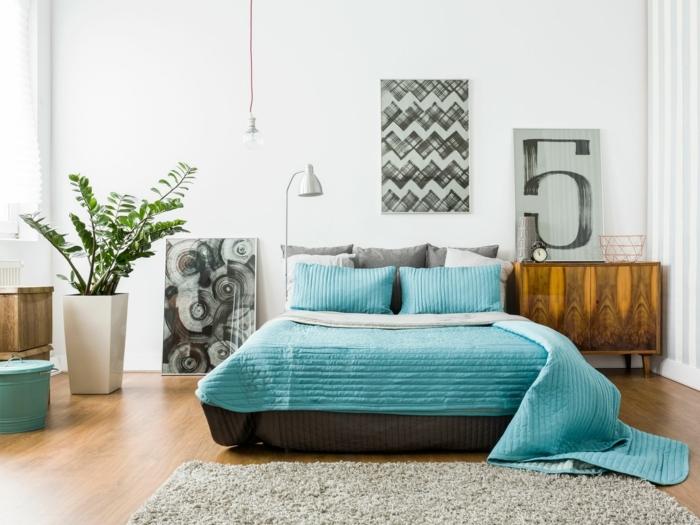 moderne Zimmer, ein Bett in blauer Farbe, grauer Teppich, abstrakte Bilder, Blumentopf mit grüner Zimmerpflanze