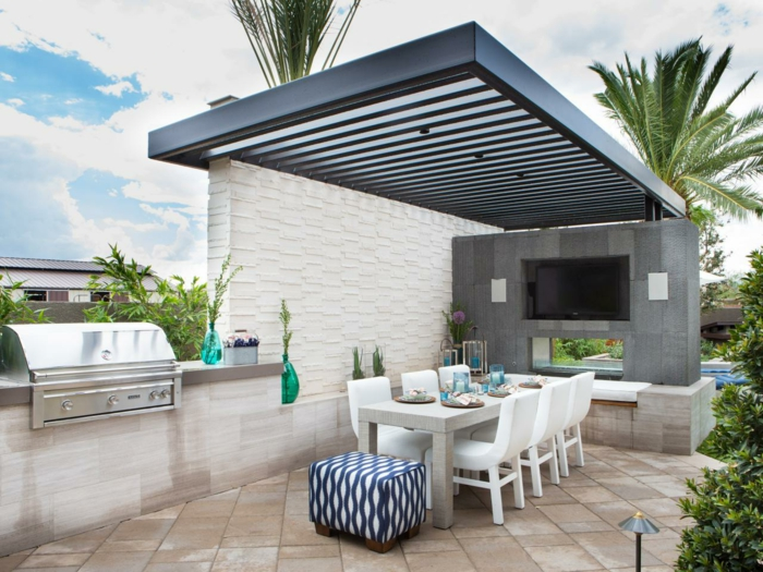 schwarze Pergola, graue Wand mit Fernseher, braune Fliesen als Bodenbelag, Blumenkübel bepflanzen