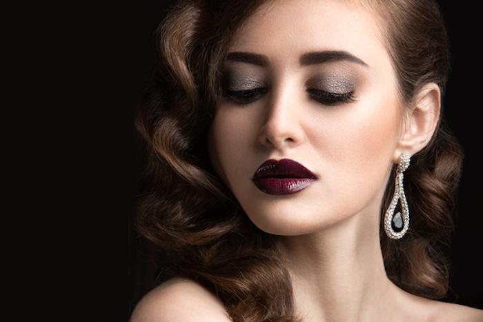 Retro Locken, weinroter Lippenstift und grauer Lidschatten, Ohrringe mit schwarzen Steinen