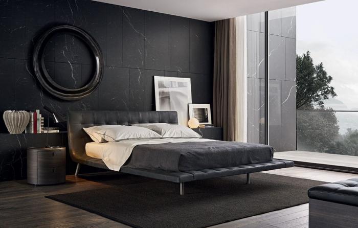 graue moderne Zimmer, graue Wände, gepolstertes Bett, graue Bettwäsche und runder Rahmen