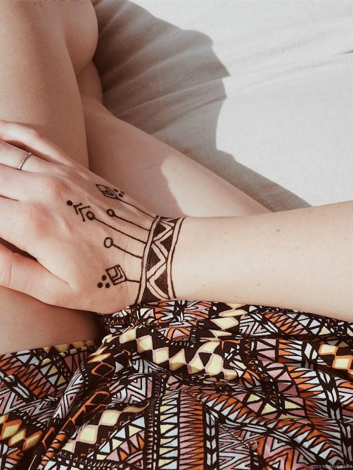 henna muster für anfänger, frau mit kleinem temporärem tattoo am handgelenk, geometrische motive