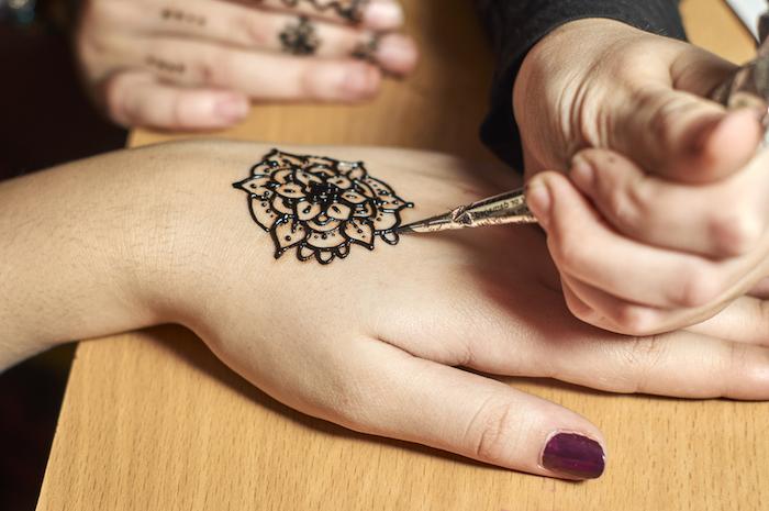 henna stift, lila nagellack, mehndi mit blumen-motiv malen, arm verzieren