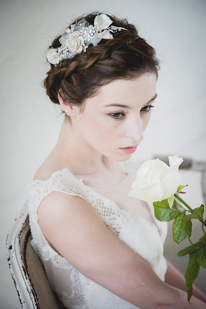 Hochsteckfrisur mit Zopfkranz, Haarschmuck mit künstlichen Blumen und Kristallen, Brautkleid mit Spitzenelementen, Porzellanteint und matte Lippen, weiße Rose