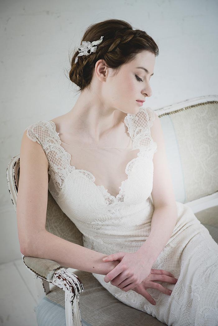 Elegantes Brautkleid mit Spitzenelementen, Hochsteckfrisur mit Zopfkranz, weißer Haarschmuck, Porzellanteint und schwarze Haare