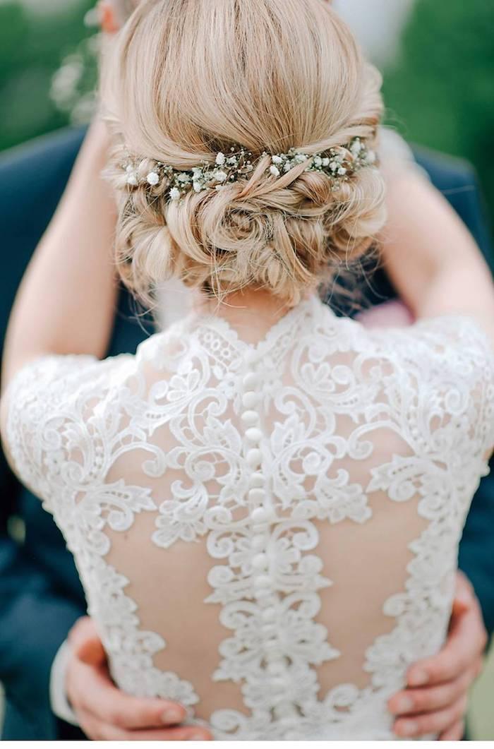 Brautkleid mit Spitzenelementen, Hochsteckfrisur mit kleinen weißen Blumen, blonde Haare