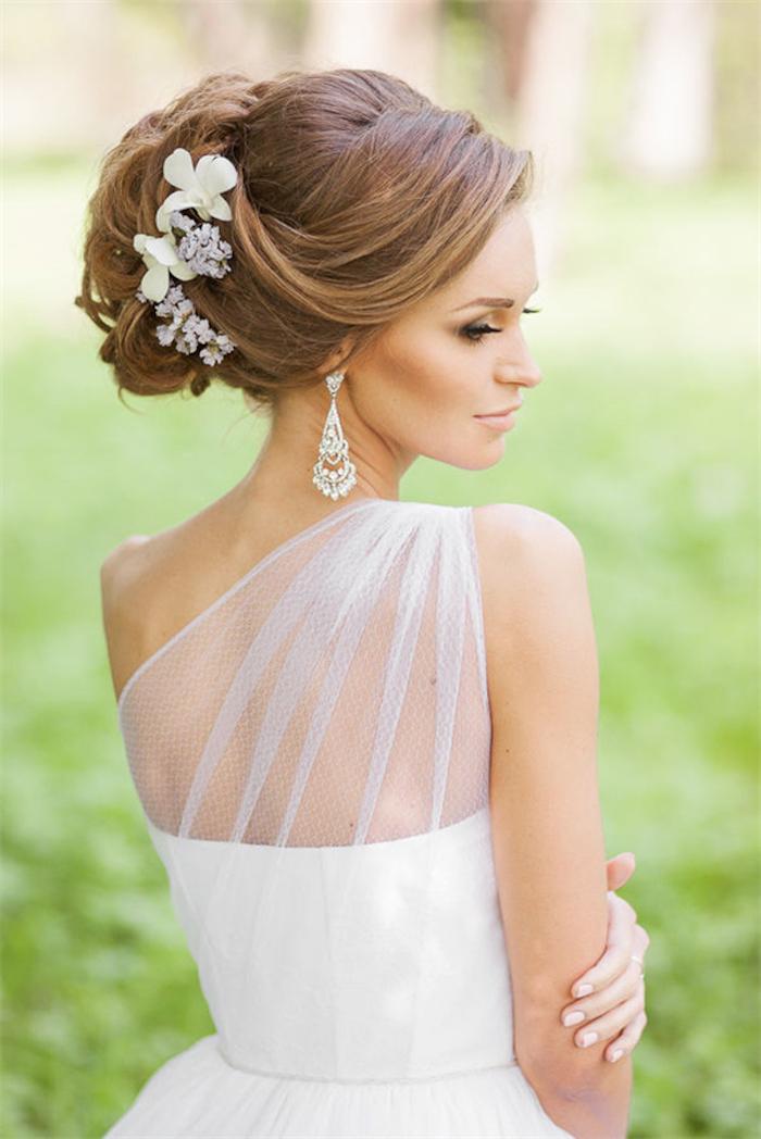 Hochsteckfrisur für lange Haare, mit echten Blumen verziert, auffällige Ohrringe mit Kristallen, Brautkleid mit Spitzenelementen