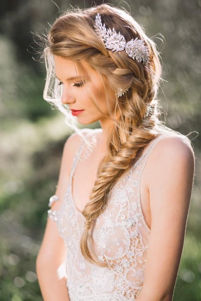 Seitlicher Fischgrätenzopf mit silbernem Haarschmuck, Brautkleid mit Spitzenelementen, olivfarbener Teint und roter Lippenstift