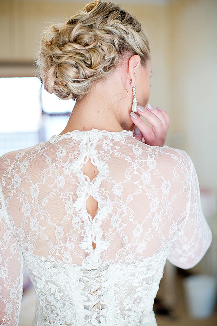 Elegante Flechtfrisur für Hochzeit, Spitzenkleid mit langen Ärmeln, lange Ohrringe mit Perlen, matter Nagellack
