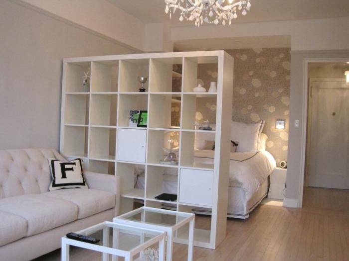 Ikea Raumteiler in weißer Farbe mit Aufbewahrungsraum, daran ein Sofa, dahinter ein Bett