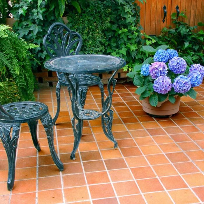 vintage Terrassenmöbel, blaue Chrysantheme, kleine rote Fliesen, Terrassen Ideen Bilder