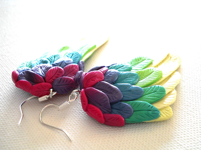 kleine ohrringe mit kleinen regenbogenfarbenen flügeln mit grünen, gelben, roten und blauen federn, fimo schmuck