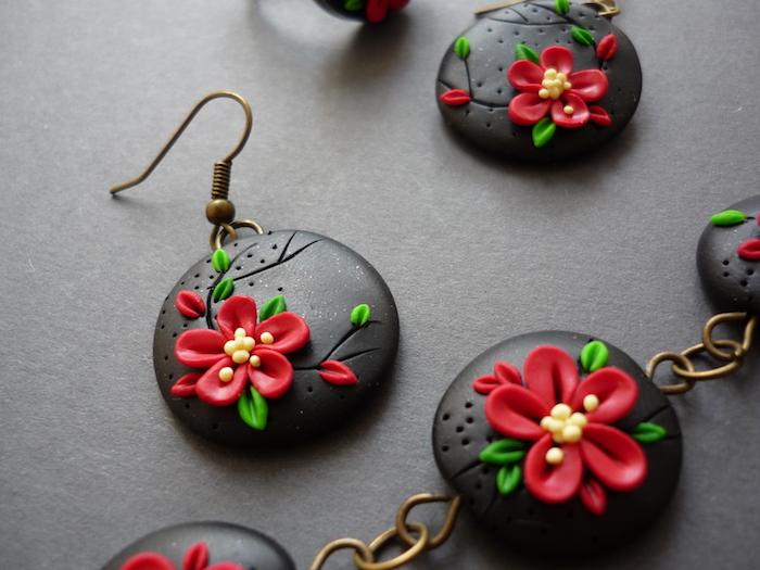 rote blumen mit grünen blättern aus fimo knete, kleine schwarze ohrringe mit fimo figuren