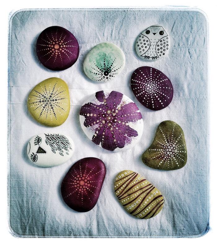drei violette bemalte steine, zwei weiße eulen mit schwarzen augen und federn, kleine eulen malen
