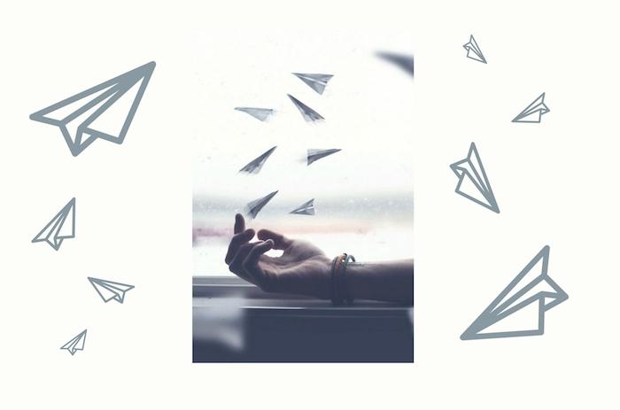eine hand mit einem armband und ein fenster, viele graue, große und kleine papierflieger, papierflieger spiele