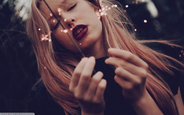 Lange blonde glatte Haare, knallroter Lippenstift und Porzellanteint, schwarzes Top