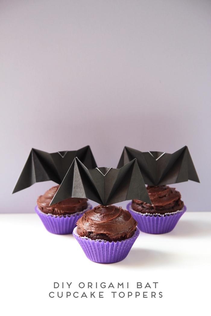 kuchen mit kleinen violetten muffinformen, drei kleine selbstgebastelte schwarze origami fledermäuse mit schwarzen flügeln aus papier, bastelideen für erwachsene