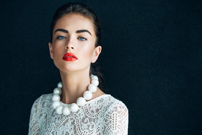 make up zum erstaunen, wasserfester lippenstift in hellroter farbe, weiße perlenkette, bluse aus spitze