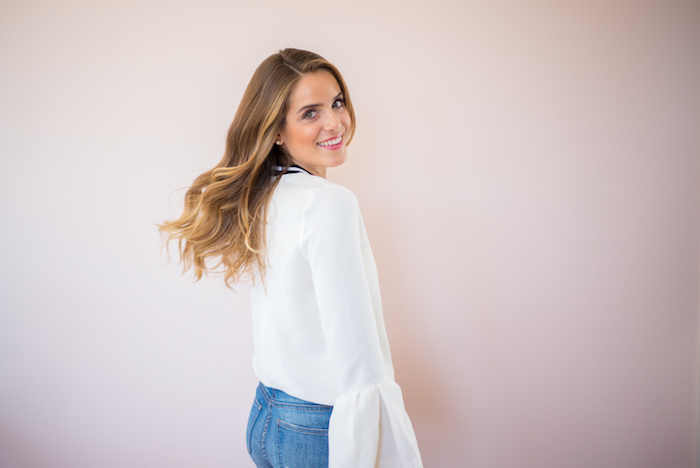 eine zufriedene frau mit langen blonden haaren, weißes hemd, jeans, kurze haare locken