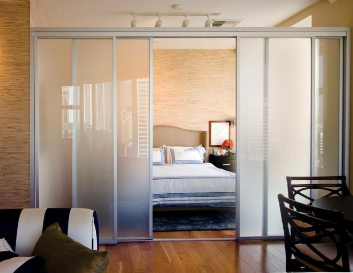 Raumtrennung mit Schiebetüren aus Glas, ein großes Bett, gestreiftem Sofa und Eszimmerstühle