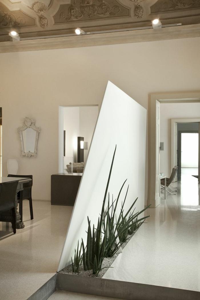 eine weiße Trennwand mit Pflanzen eine grüne Raumtrennung zwischen Flur und Esszimmer