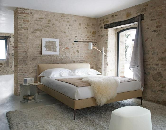 ein Schlafzimmer im Altbau, moderne Zimmer mit Naturstein Optik Wände, weißes Bett